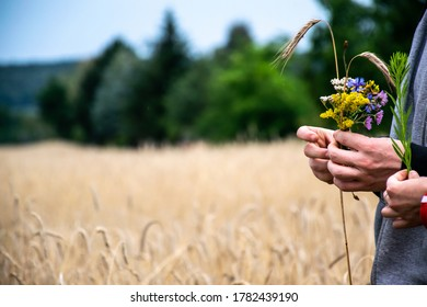 Picture of hand holding a flower bouquet with wheat field in the background.