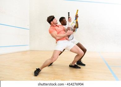 Picture of handsoe men playing squash on court. Young man playing guitars indoors. Sports and entertainment concepts.