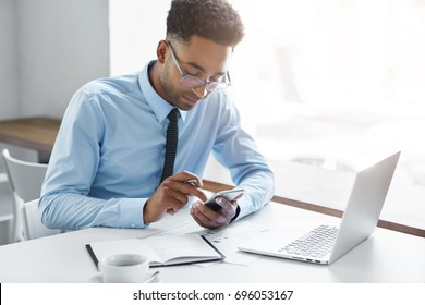 Picture of handsome African office worker having a few minutes break, texting sms on smart phone, sitting at his workplace with generic laptop computer, papers, notebook and mug of coffee on table