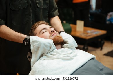 Picture of handsome bearded man getting beard shaving by hairdresser while lies in chair at barbershop.