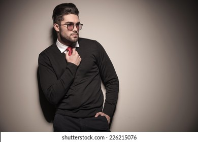 Picture of a handsome business man looking away from the camera while fixing his tie.