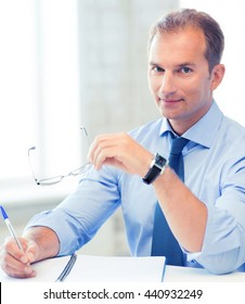 picture of handsome businessman with spectacles writing in notebook