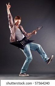 Picture of handsome guitarist making a rock gesture and keeping a leg up