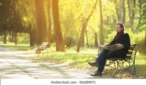 Picture of handsome man in black coat sitting on the bench and reading newpaper in the park. Man spending his weekends with autumn.