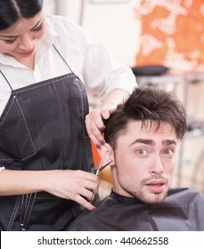 Picture of handsome man having his hair cur by professional hairdresser in hairdressing saloon. Young man looking at camera.