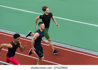Picture of handsome multiethnic athlete group run on running track outdoors. Looking aside.