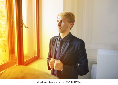 Picture of handsome young blond european man, wears formal outfit. Serious and anxious  office worker in luxury suit is standing behind the window in modern office. Concept of succesful man.