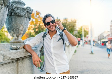 Picture of handsome young  businessman talking on phone smiling. Cheerful male in the street on Mobile phone. Technology, communication and people concept.  Overjoyed smiling man talking on cell phone