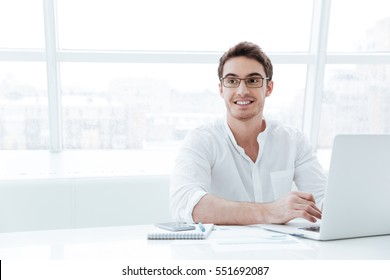 Picture of handsome young man dressed in white shirt using laptop computer. Look aside.