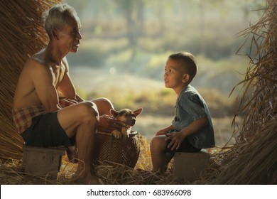 Picture of Happiness family, Grandpa and child taking a rest from the farming to do a storytelling.