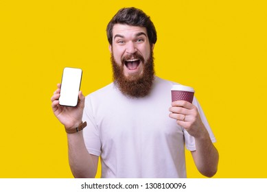Picture of happy bearded man standing isolated over yellow background drinking coffee and showing  mobile phone.