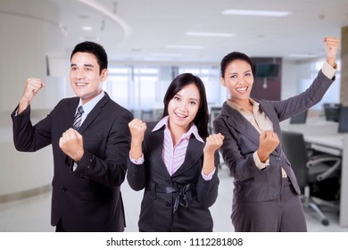 Picture of a happy business team lifting hands to celebrating their triumph in the office