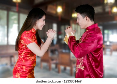 Picture of happy Chinese couple congratulating each other while standing at home