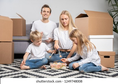 Picture of happy couple with children eating rice with shrimps sitting on floor