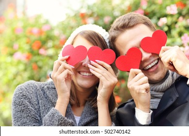 Picture of happy couple covering eyes with hearts