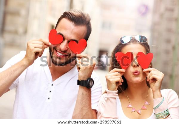 Ein Bild eines glücklichen Paares, das Augen mit Herzen bedeckt