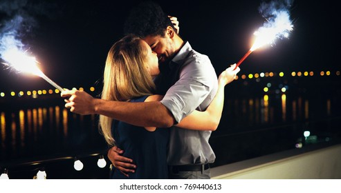 Picture of happy couple holding burning sparkle