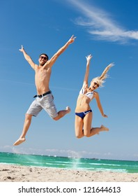 picture of happy couple jumping on the beach (focus on woman)