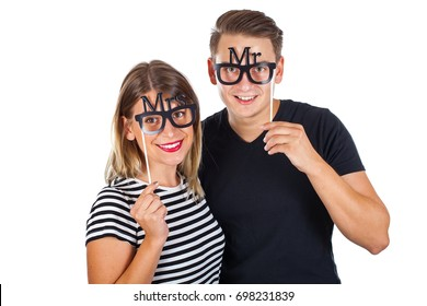 Picture of a happy couple posing with photobooth accesories on isolated background