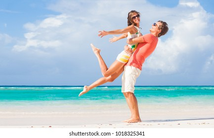 picture of happy couple in sunglasses hugging on the beach