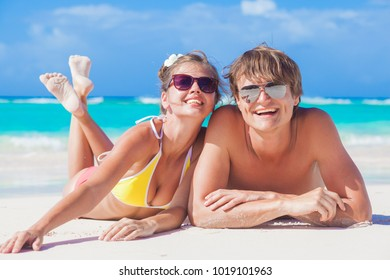 picture of happy couple in sunglasses lying on the beach