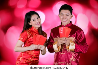 Picture of happy couple wearing cheongsam clothes while holding envelopes and standing with blurred sparkling light background