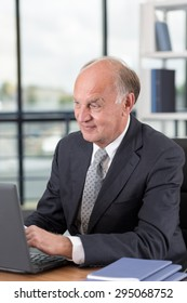 Picture of happy elderly man in suit working on laptop
