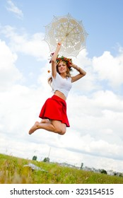 Picture of happy excited girl in flower wreath jumping on summer meadow. Young amazing woman with lace umbrella on blue sky countryside background.