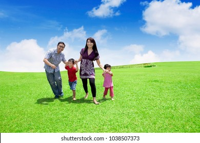 Picture of happy family playing together while running in the meadow with beautiful sky background