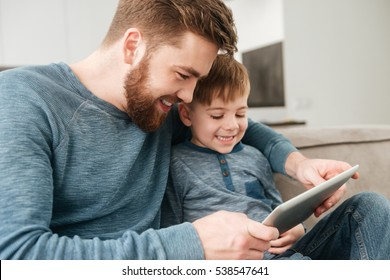 Picture of happy father using tablet computer with his little cute son.