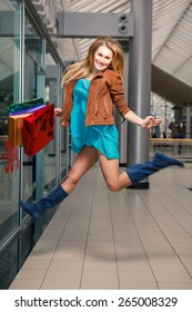 picture of happy girl  jumping with shopping bags  in the mall.