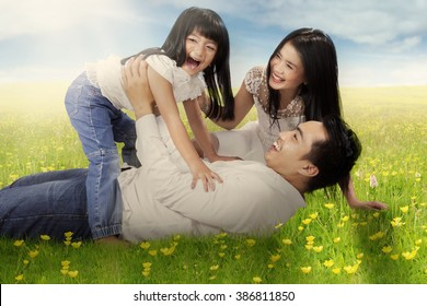Picture of happy little girl and her parents playing and laughing together on the meadow at springtime
