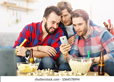 Picture of happy male friends cheering and watching sports on tv