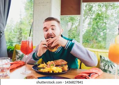 Picture of happy man eating vegan burger in vegan restaurant or cafe. Smiling man sitting at table.