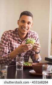 Picture of happy man eating vegan burger in vegan restaurant or cafe. Smiling man sitting at table and looking at camera.