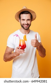 Picture of happy man in summer hat with cocktail looking camera isolated showing thumbs up.