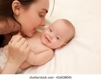 Picture of happy mother with adorable baby lying on bed
