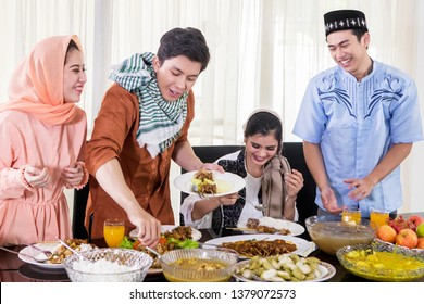 Picture of happy Muslim people eating foods during break the fast together in the dining room. Shot at home