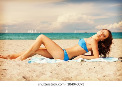 picture of happy smiling woman laying on a towel