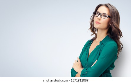 Picture of happy smiling young business woman in green confident clothing and glasses, with empty copy space place for some text, advertising or slogan, over grey background