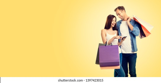 Picture of happy smiling young couple with shopping bags, and smartphone, against yellow color backround. Copy space for some slogan or advertising text. Caucasian models - online shopping concept.