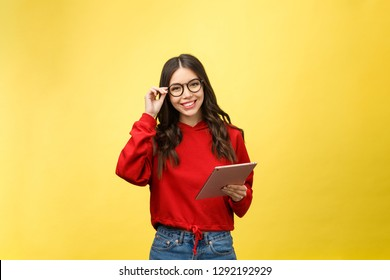 Picture of happy teenage girl with tablet pc computer isolate on yellow background