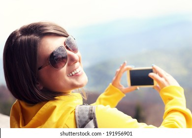A picture of a happy tourist taking pictures in the mountains