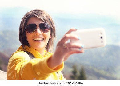 A picture of a happy tourist taking selfie in the mountains