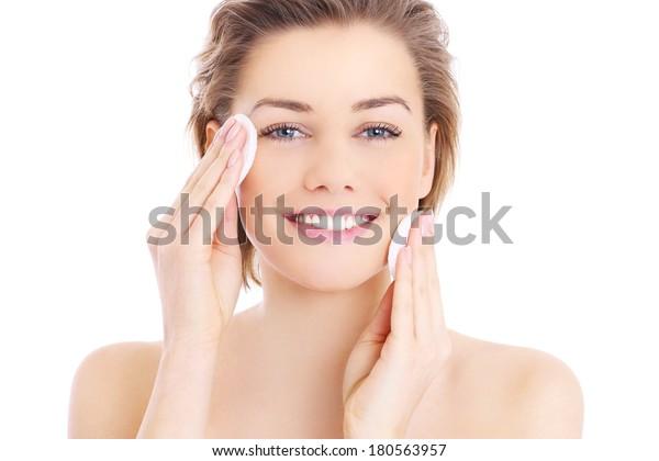 Фотография счастливой женщины, очищающей лицо с ватным тампоном на белом фоне