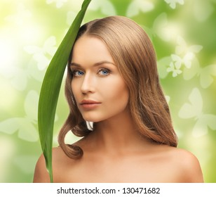 picture of happy woman with green leaf and butterflies