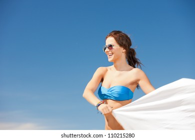 picture of happy woman with white sarong on the beach.