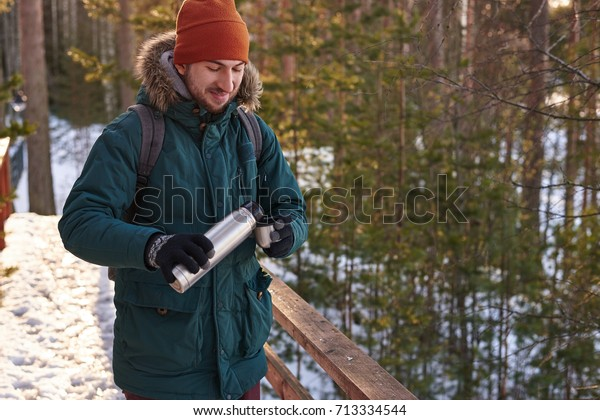 Picture of happy young bearded European backpacker wearing gloves, hat and coat with fur hood drinking hot beverage outdoors while hiking in winter woods, holding thermos of tea or coffee and mug.