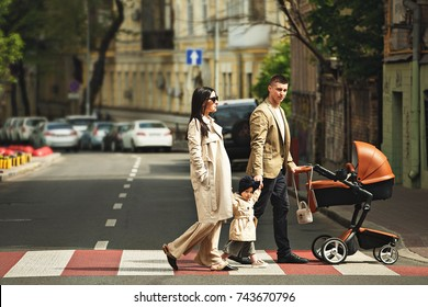 A picture of a happy young family on a walk on a day off. A happy family crosses the road at a pedestrian crossing.