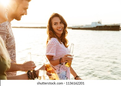 Picture of happy young friends outdoors on the beach drinking beer.